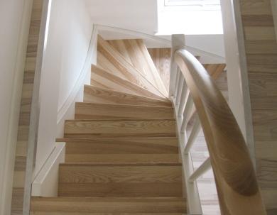 Jesionowe stopnie białych schodów